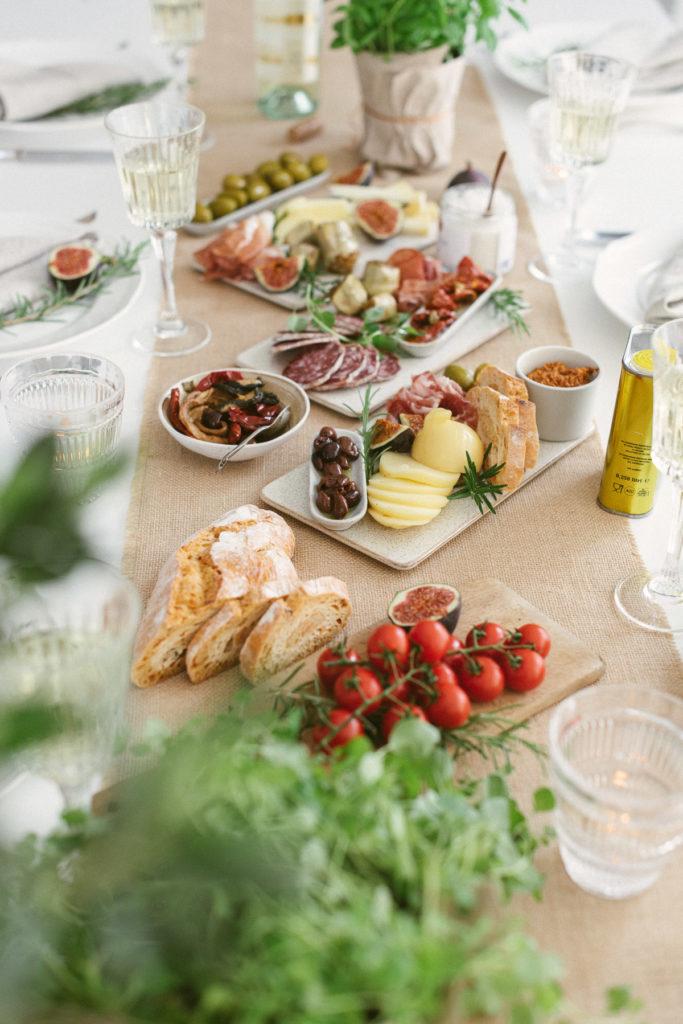 Gedeckter Tisch mit 3 Servierplatten und Antipasti