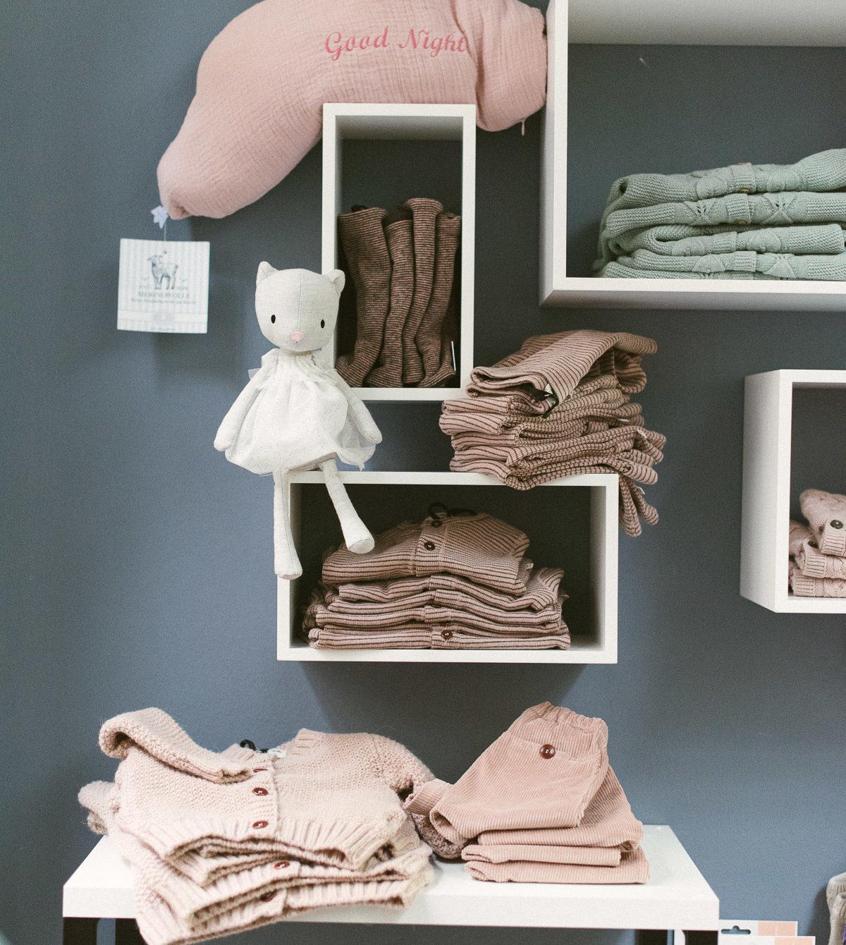 Wand mit Regalen und Kinderkleidung